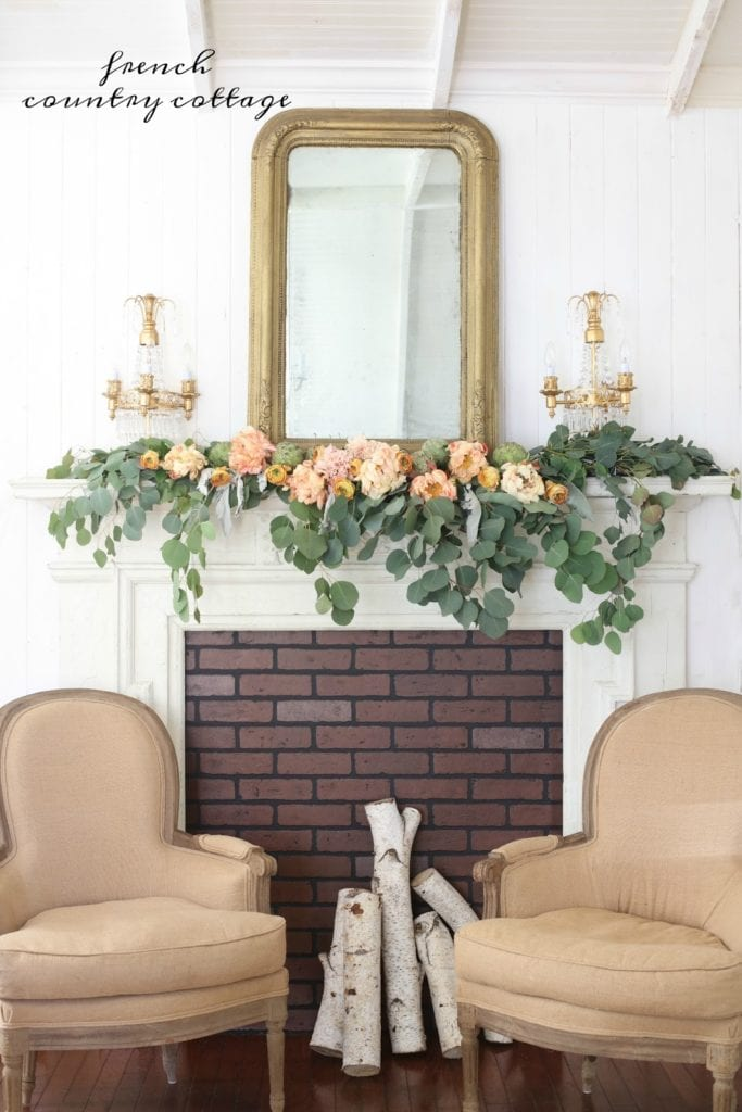 fresh flowers on the mantel with chairs and birch logs for autumn