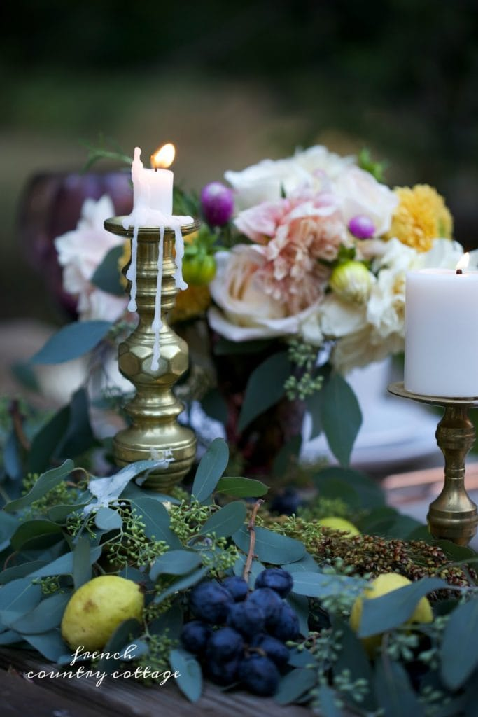 candle with wax and fresh eucalyptus and grapes on autumn table