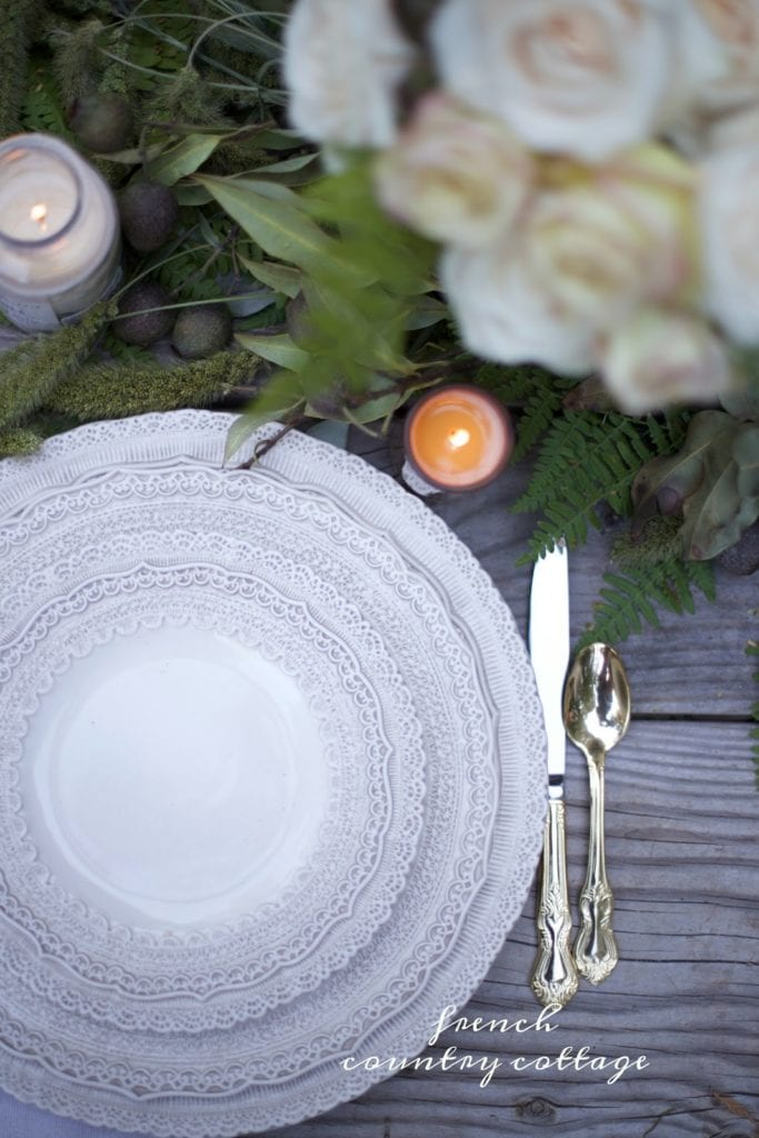 beautiful plates, gold flatware and greens on table