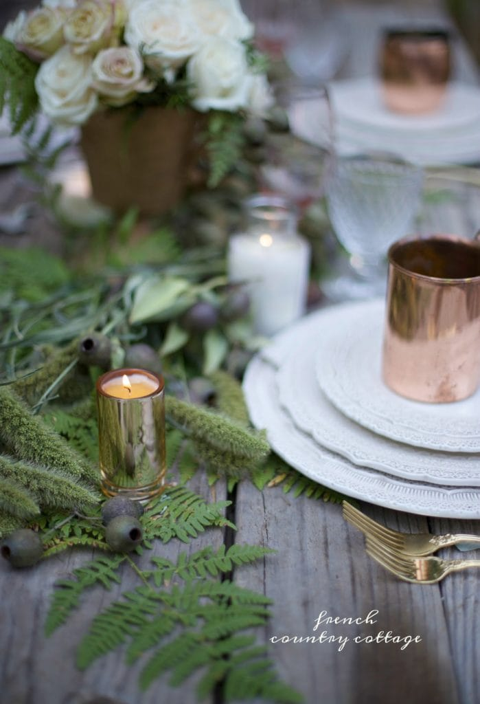 fresh greens and copper on table setting