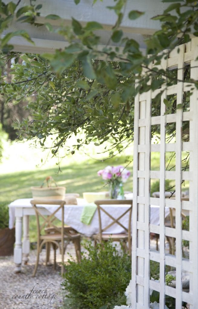 Garden arbor with table setting on pea gravel patio