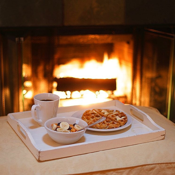 waffles, fruit and coffee next to fireplace