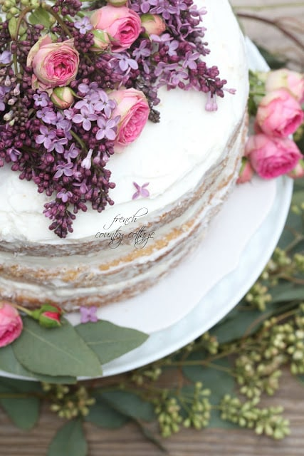 rustic cake topped with lilac and roses
