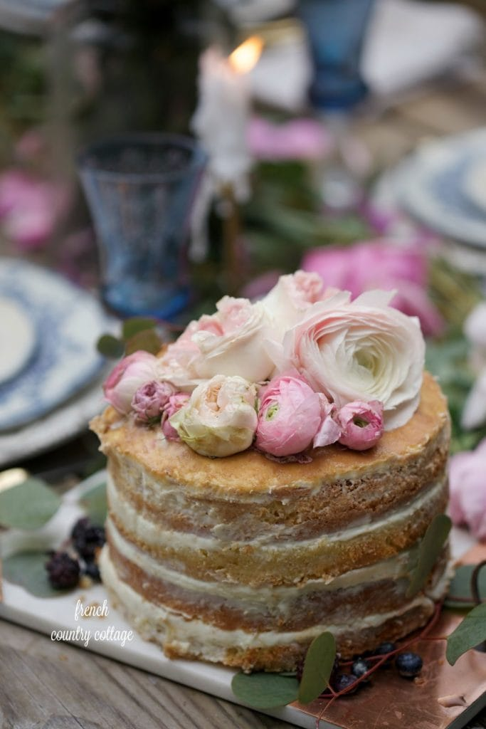 Romantic table setting with naked cake topped with fresh flowers and berries