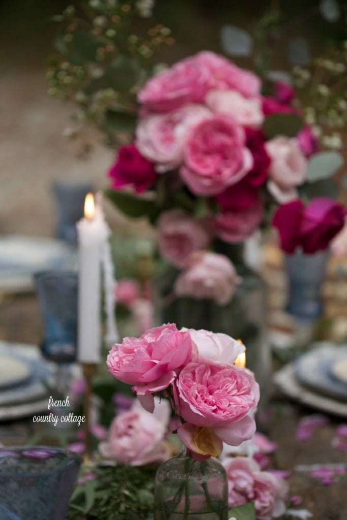 Table centerpiece with blush roses in glass bottles