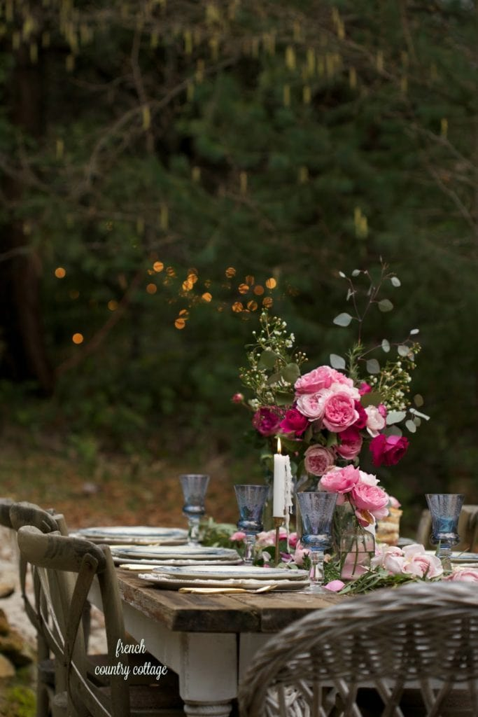 Outdoor romantic table setting with flowers and twinkly lights