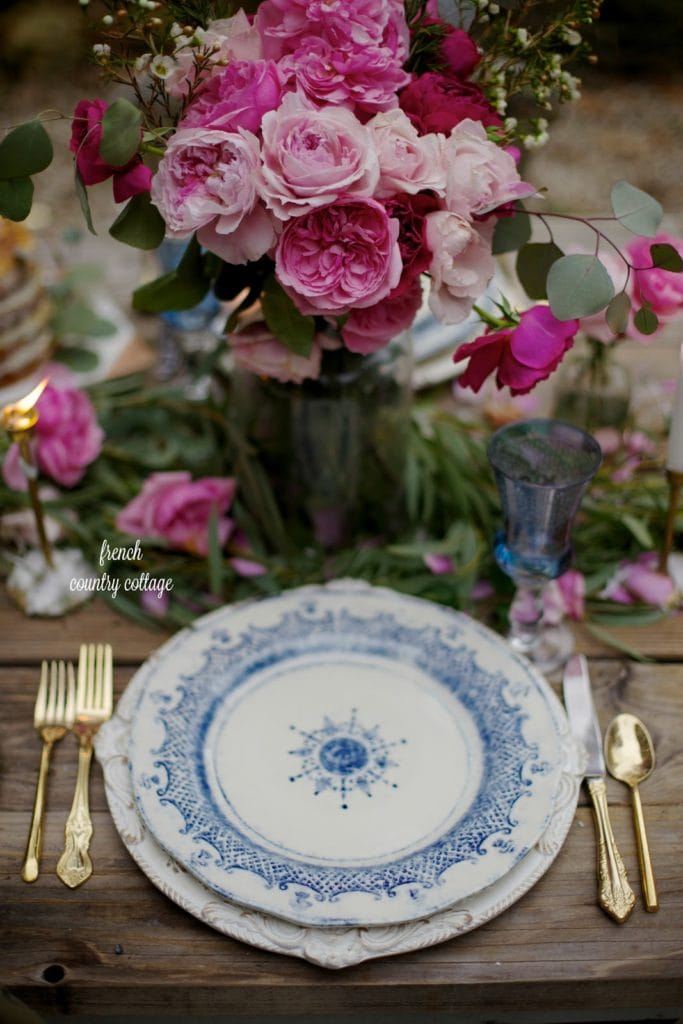 Blue and white place settings, gold flatware and flowers for Valentine's Day table