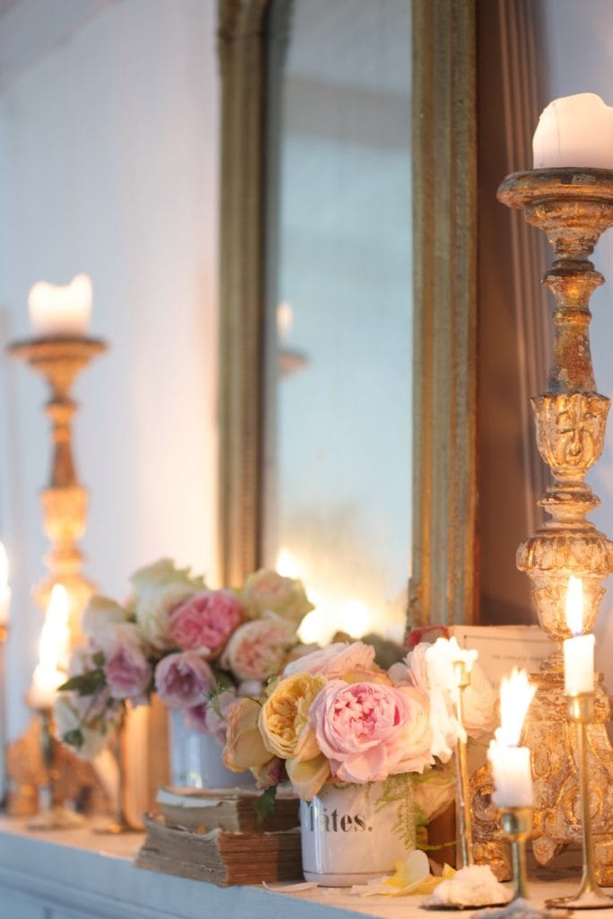 Evening light from candles on fireplace mantel and flowers
