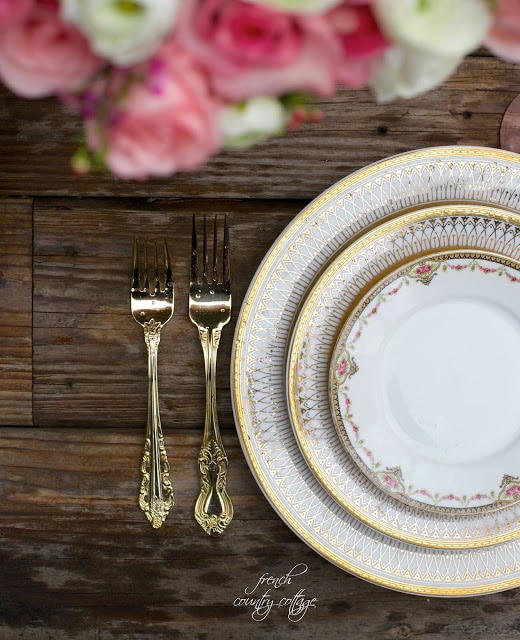 gold dishes and flatware on rustic table top