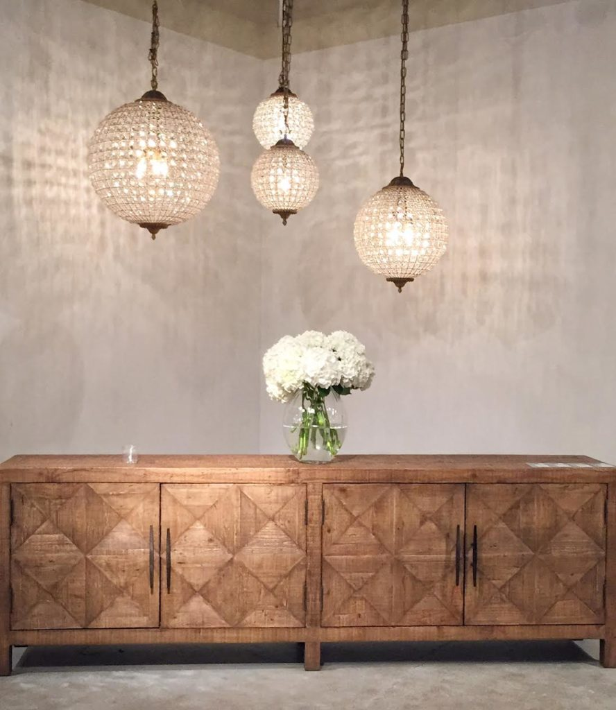 Grouping of chandeliers above natural finished sideboard