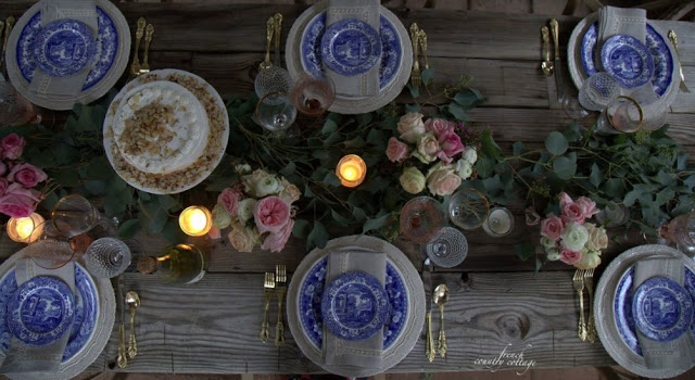 blue and white dishes with candles and flowers on table