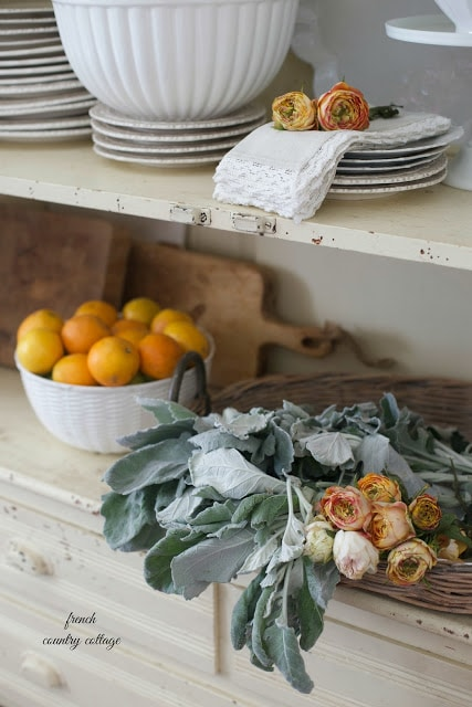close up of oranges and flowers on shelves