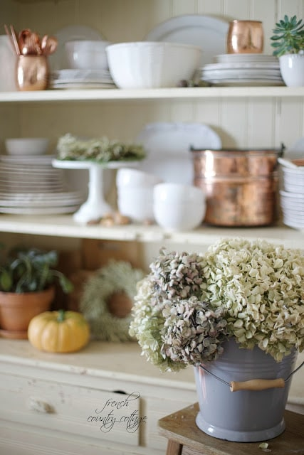 autumn display with white dishes and hydrangeas