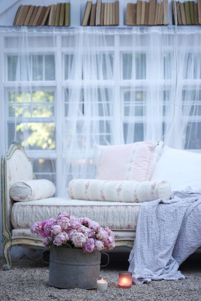 gravel floor shed with bucket of peonies and daybed