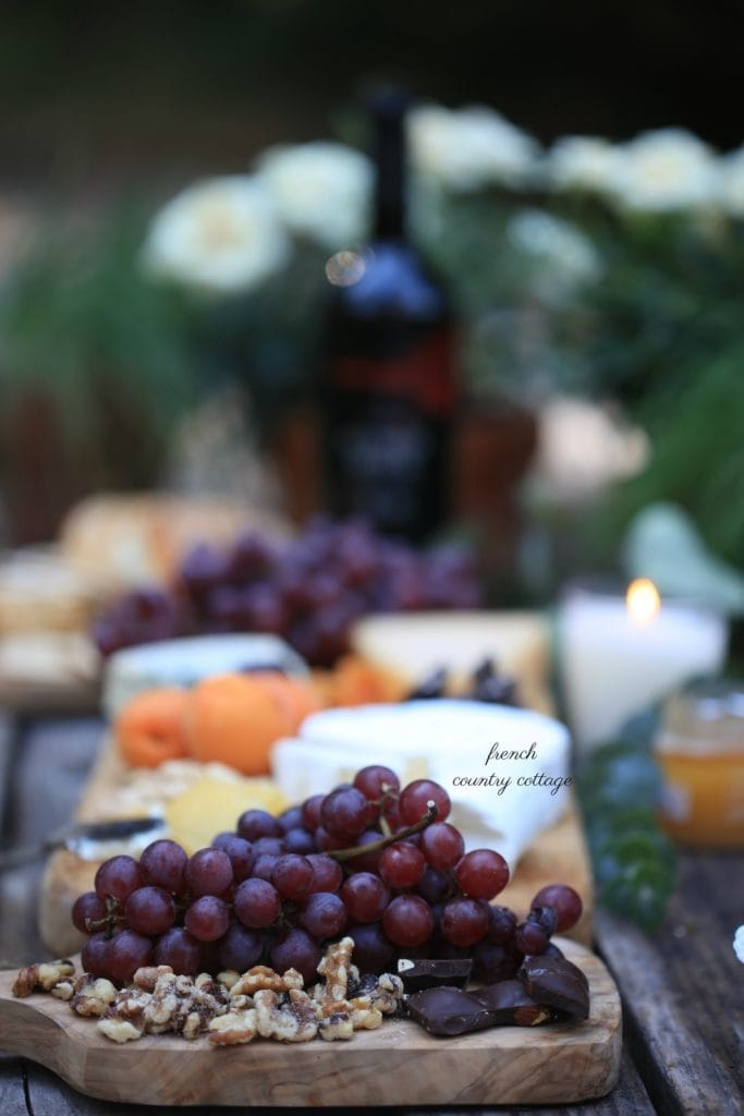 red grapes and cheese with walnuts on cheese board