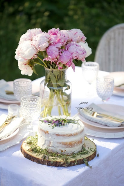 outdoor table setting with fresh flowers and rustic cake