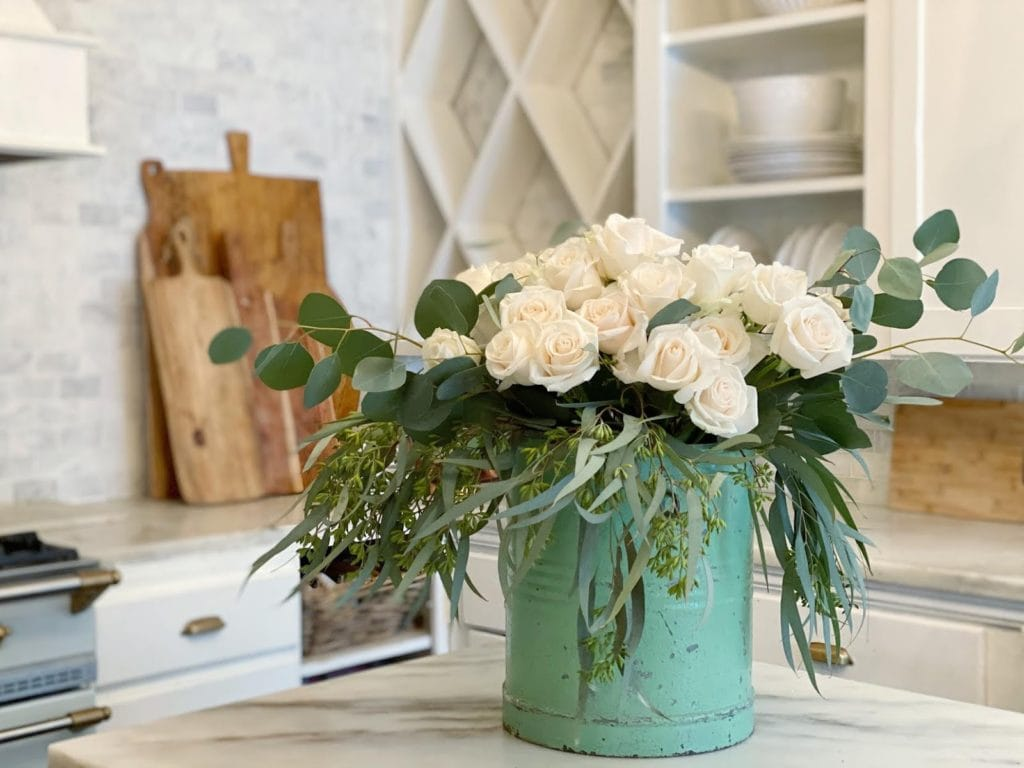 white roses and eucalyptus in kitchen
