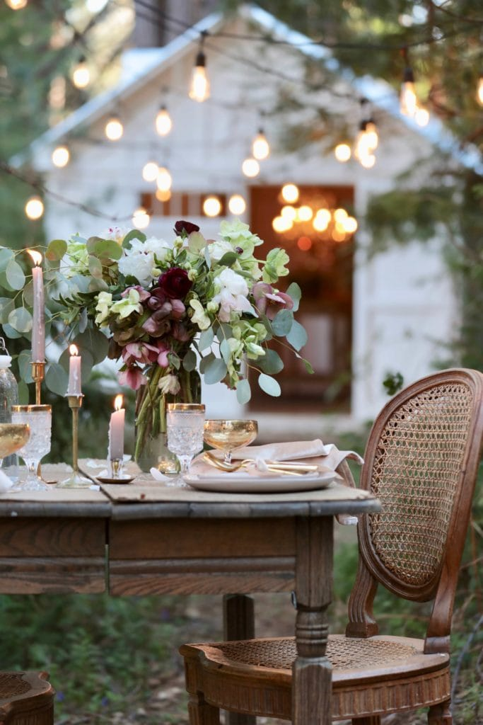 Barn with twinkle lights and table setting in front of it.