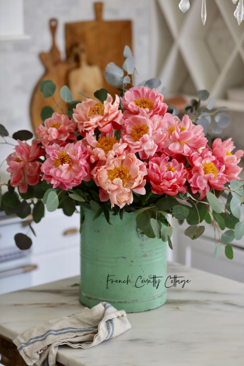 coral peonies in green vintage bucket