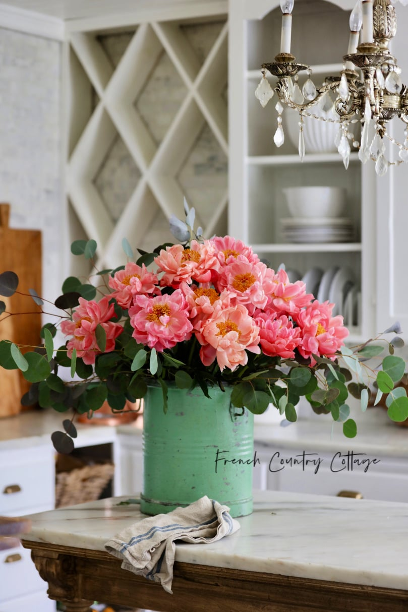 Coral peonies in a vintage green bucket in the kitchen