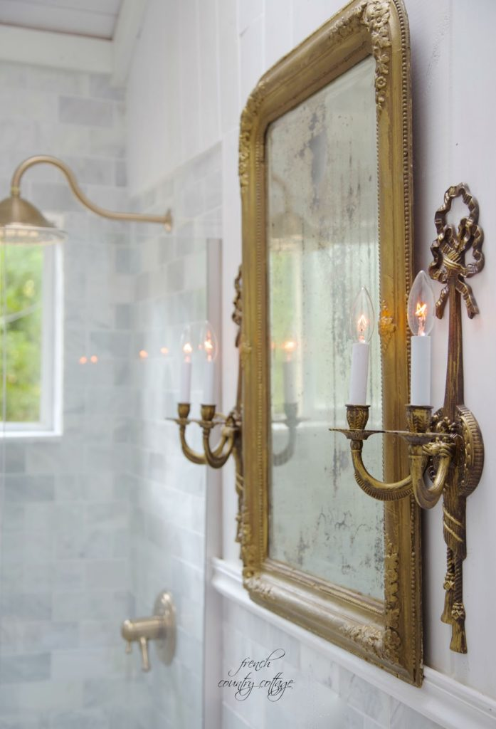 French style sconces and vintage mirror in bathroom