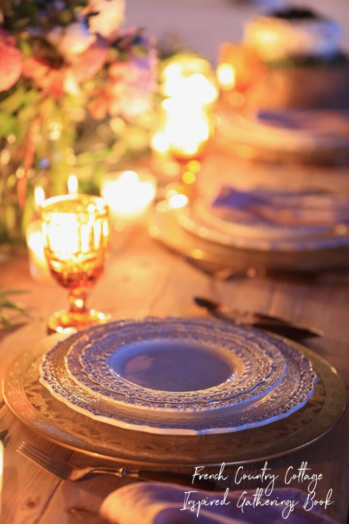 Evening close up of dishes on table in book French Country Cottage Inspired Gatherings