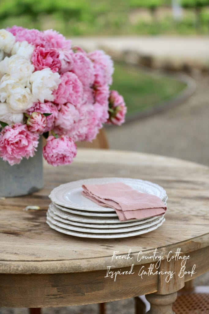 Stack of dishes and peonies on table