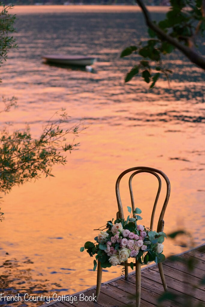 Chair with flowers on dock at sunset