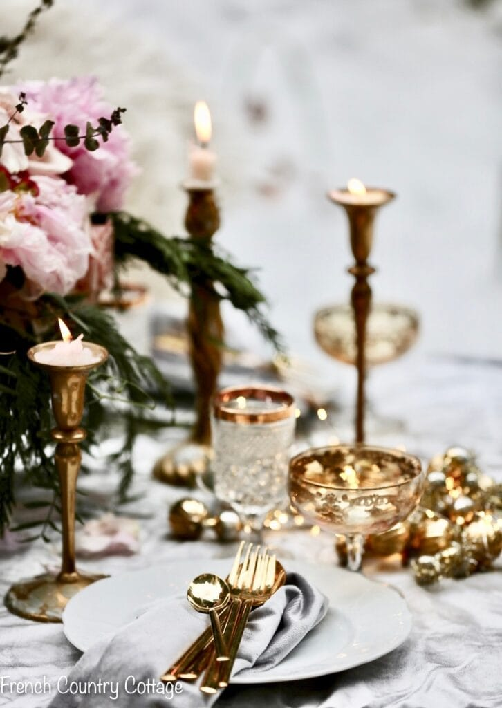 Gold candles and garland on velvet tablecloth