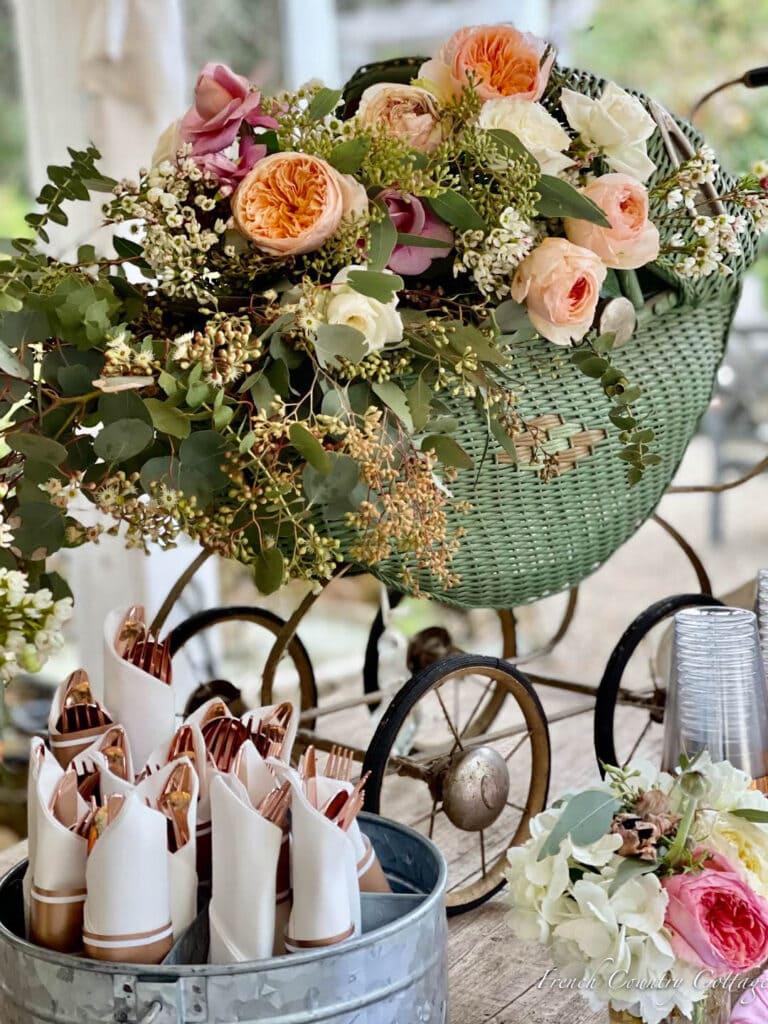 antique doll buggy flower arrangement on table