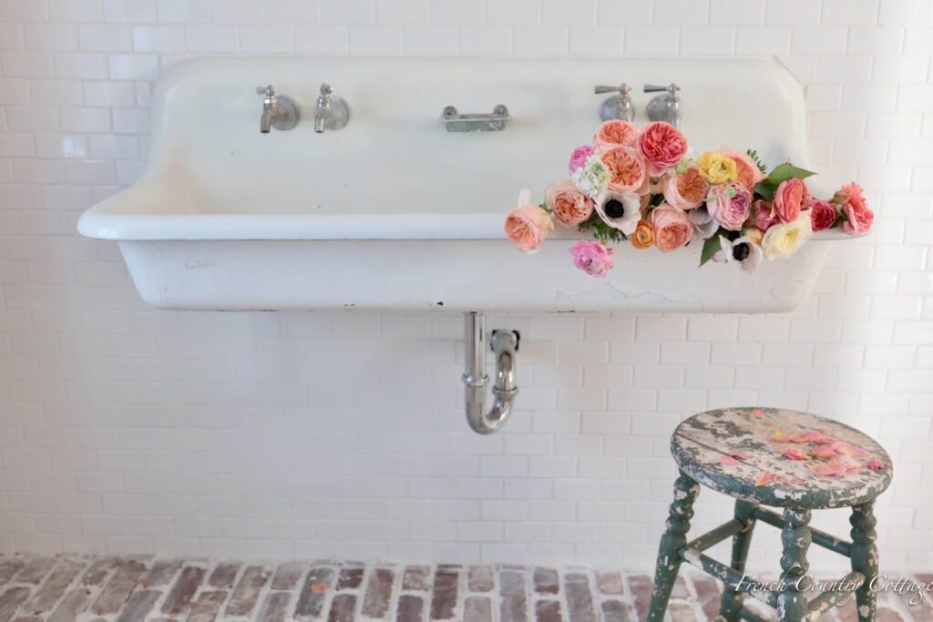 Antique Farm Trough sink in bathroom with subway tile walls and brick floor