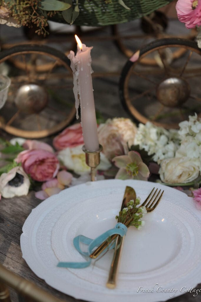 close up of place setting with ribbon tied flatware and wax covered candle