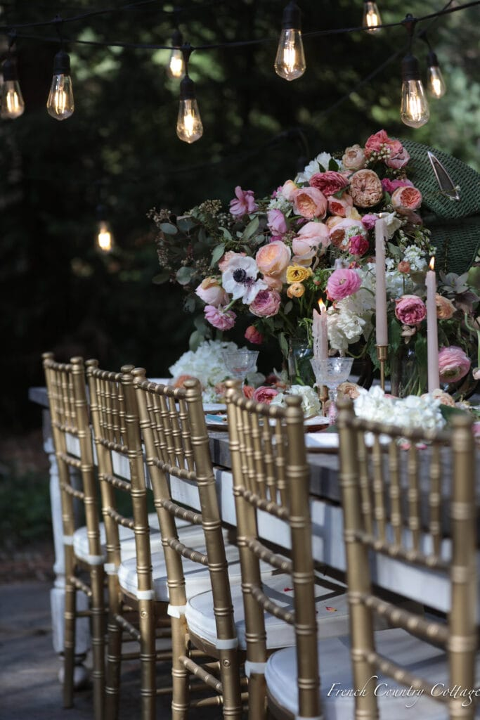 gold chairs at outdoor dining table with elegant flowers