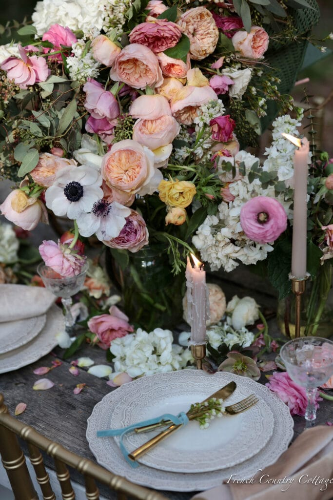 Blush taper candles on dining table with flowers