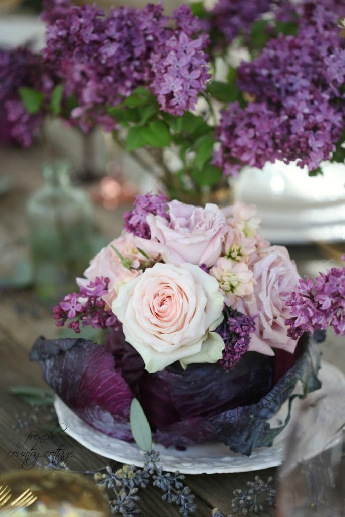 purple cabbage filled with flowers on table