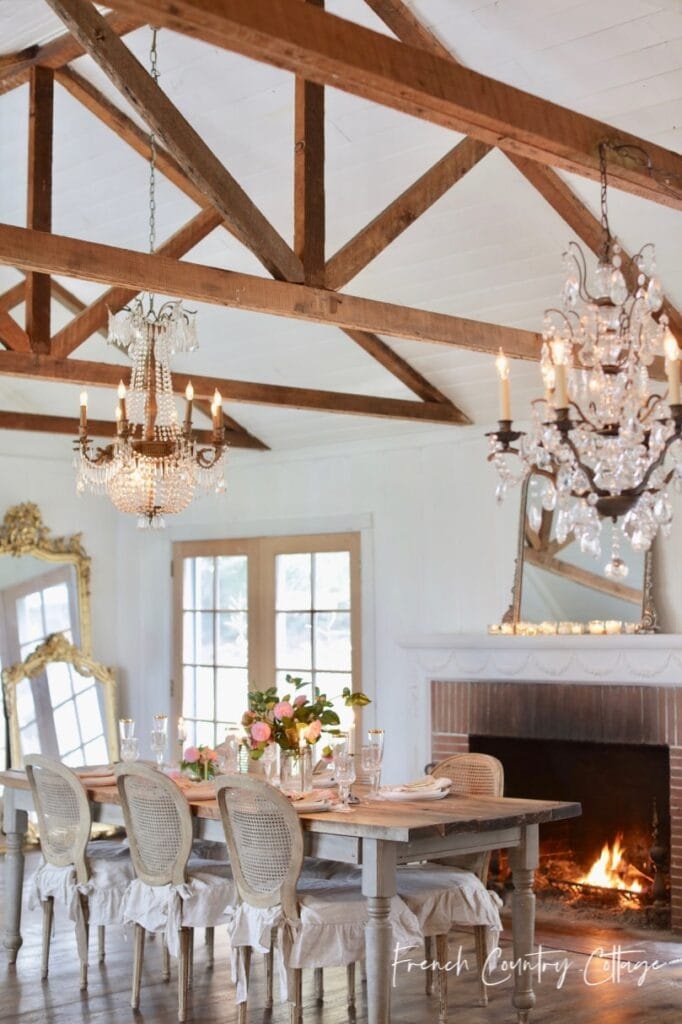 Living room and dining room with open beams and chandeliers