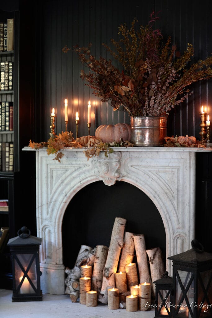 fall mantel with leaves and books in living room