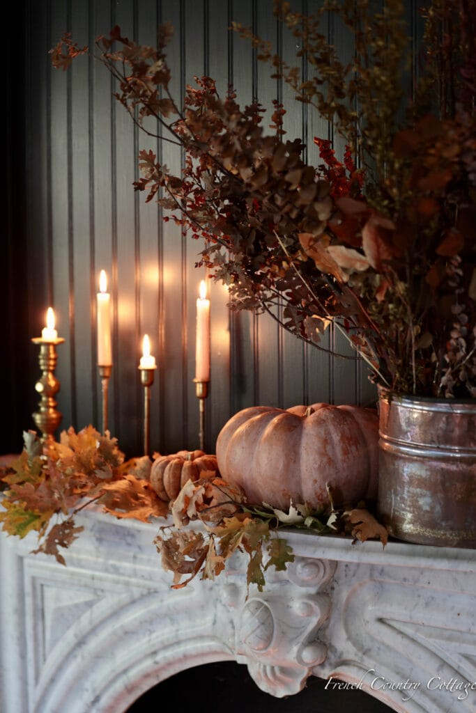 Foraged branches and candles on a mantel for autumn